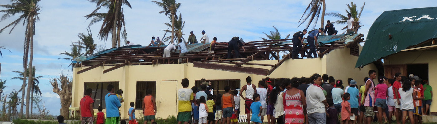 Local villagers helping to repair a storm damaged house