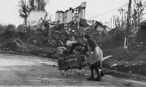 World War 2 refugees pushing a cart against the backdrop of a bombed out building