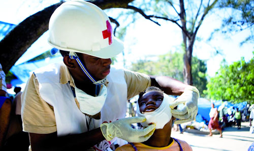A medical practitioner treats a young injured boy.