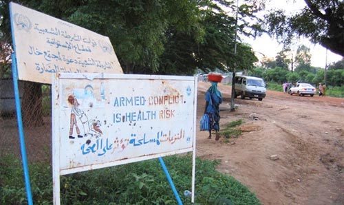 'Armed conflict' warning sign in foreground, and people going about daily business in the background.