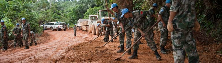 UN peacekeepers repairing a water damaged mud road.