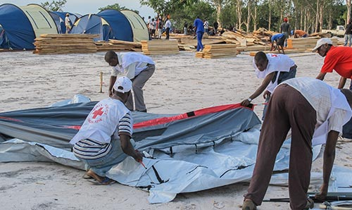 Red Cross workers putting up a tent in a new refugee camp in Congo, Central Africa / Editorial Credit: Chris Warham / Shutterstock.com